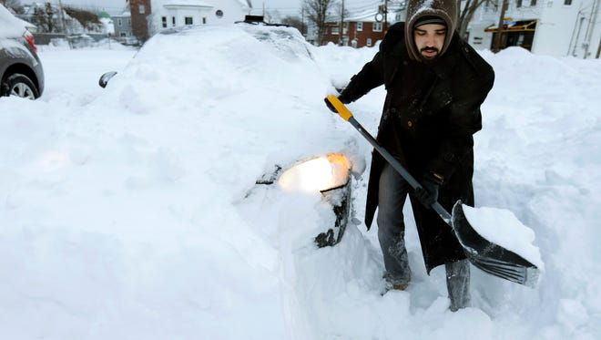 Fabricio Calazans digs his car out of piled snow to go to work, Wednesday, Jan. 28, 2015, in Norwood, Mass., after a winter snowstorm slammed New England on Tuesday.