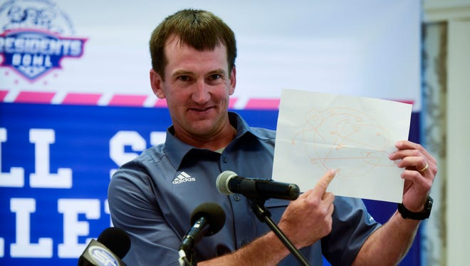 Jayson Poppinga, head football coach at O'Gorman, holds up a game plan drawn by his daughter for his team's game against No.1 Washington on Saturday. Coaches, boosters and local politicians gathered Wednesday for the friendly President's Bowl luncheon before the schools meet Saturday at Howard Wood Field.