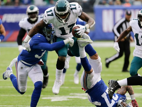 Philadelphia Eagles wide receiver Alshon Jeffery (17) leaps over New York Giants free safety Darian Thompson (27) as cornerback Andrew Adams (33) makes the tackle during the second half of an NFL football game, Sunday, Dec. 17, 2017, in East Rutherford, N.J.