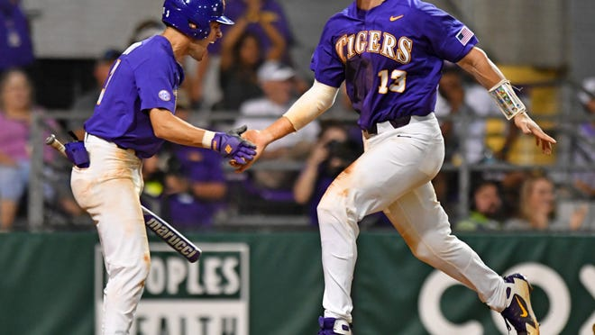 LSU's Saul Garza, left, greets Hal Hughes, who scored on a single by Chris Reid during the eighth inning against Southern Mississippi during an NCAA college baseball tournament regional game Saturday, June 1, 2019, in Baton Rouge, La. (Hilary Scheinuk/The Advocate via AP)