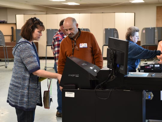 At right, Poll Inspector Richard Wilson assists Elizabeth Satterlee with the voting machine in Wappingers Falls on Tuesday.