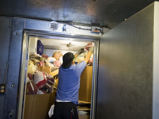 David Cordova puts frozen turkeys in a freezer during a food drive at the Phoenix Rescue Mission on 35th Avenue in Phoenix on Saturday, Nov. 12, 2016.