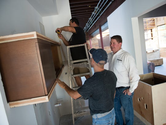 Straticon CEO Jeff Hardin (right) works with contractors installing cabinetry.