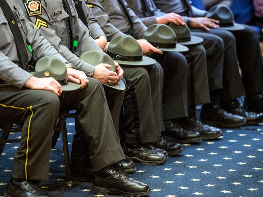 Pennsylvania State Troopers sit while listening to