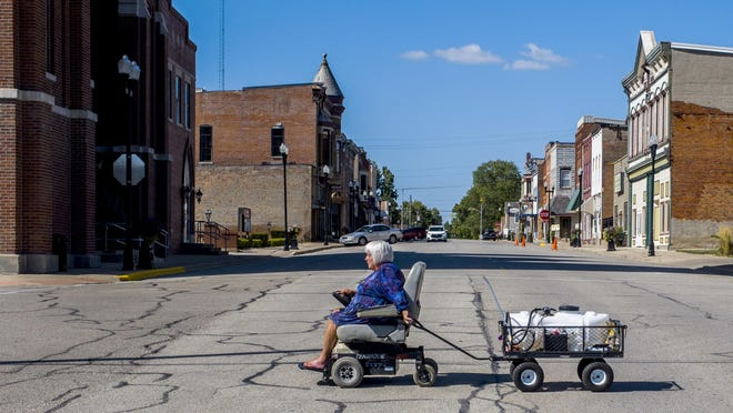 Connie Madden, 74, crosses Locust Street in Delavan on Thursday pulling her wagon bearing a five-gallon container of water. Madden has been caring for the planters that line some of the community's downtown streets in a daily ritual of sprucing up and watering of six large pots and 15 smaller pots.