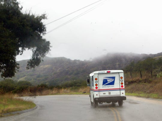 FILE: A U.S. Postal Service truck drives along a road near Salinas in 2014.