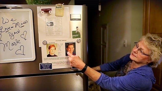 Maureen Himebaugh points to an old and age-enhanced photo of her missing son Mark on the refrigerator at her Del Haven home.