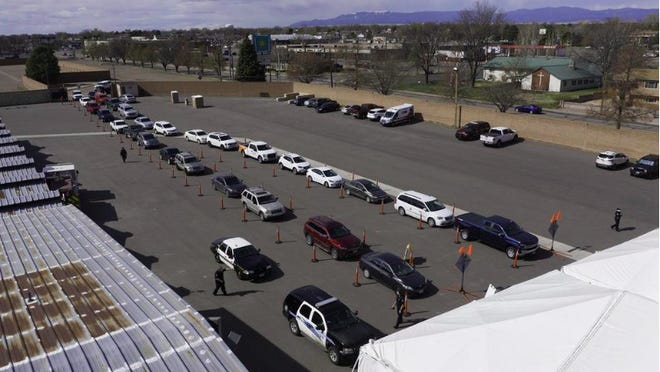 Vehicles enter the Colorado State Fairgrounds in April for drive-thru COVID-19 testing. The hours and days of operation for testing are now being expanded.