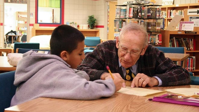 Longtime Holland Public Schools educator Richard Rust working with then fifth-grader Andres Saldivar in 2011.