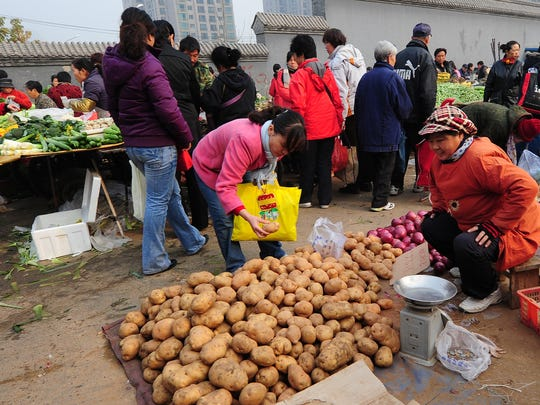 People shop for produce at an outdoor vegetable and