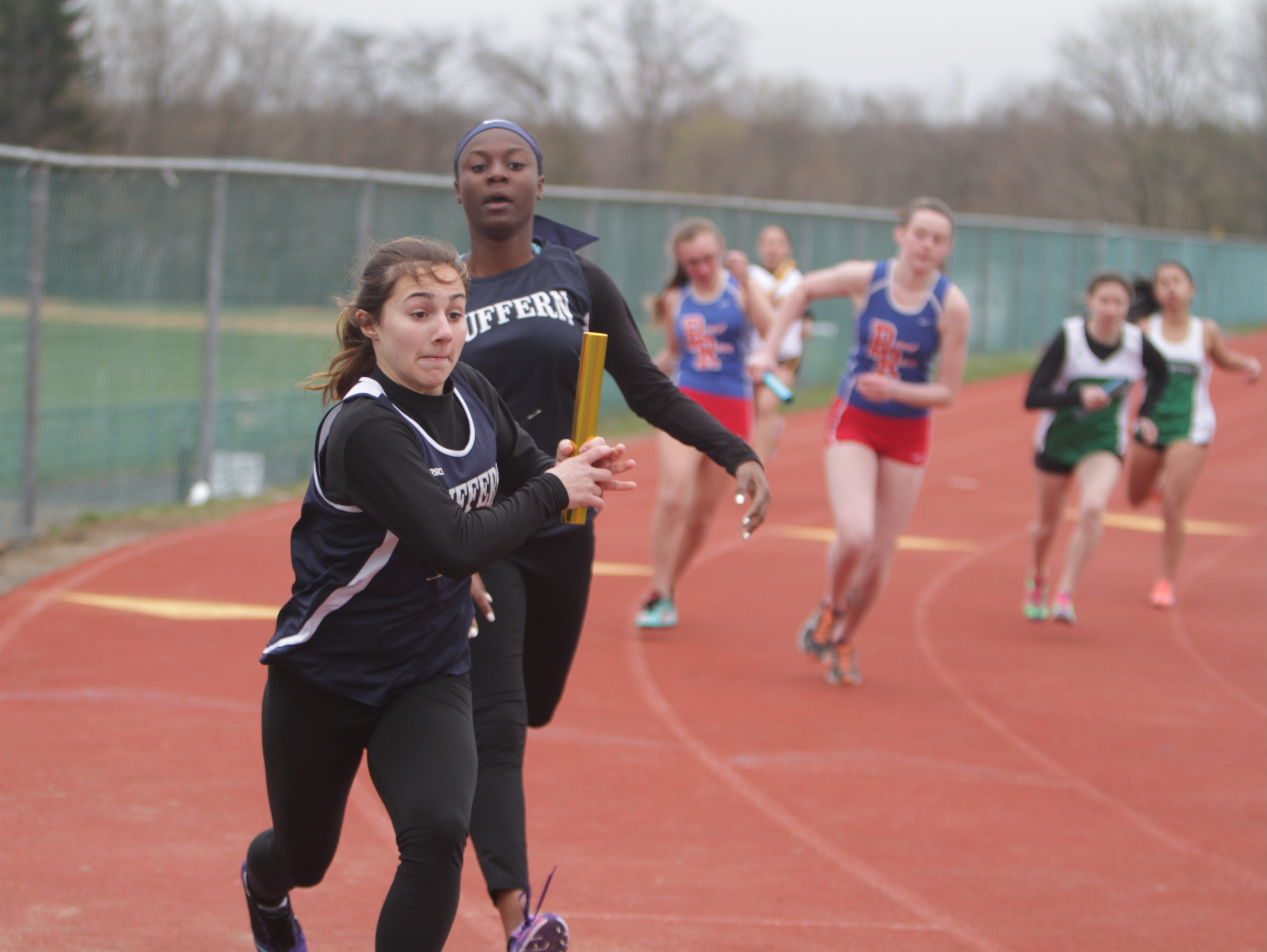 Suffern's Nadia Nelson (second from right) hands off the baton to teammate Catherine Jones during the Nanuet Relays at Nanuet High School on Saturday, April 9th, 2016.