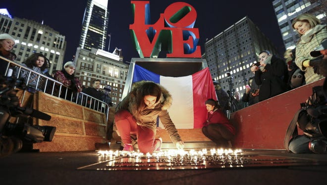Cloe Tinchant lights candles in LOVE Park in Philadelphia on Nov. 14, 2015, during a vigil to remember the victims of the attacks in Paris.