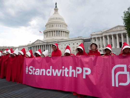 "Supporters of Planned Parenthood dressed as characters from ""The Handmaid's Tale,"" hold a rally outside the US Capitol in Washington, DC, June 27, 2017."