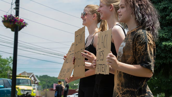About 30 peaceful protesters gathered at Tallmadge Circle Tuesday afternoon to show their support for the Black Lives Matter movement. Pictured from left are: Jasmine Grimm, 18, Grace Grimm, 18, and Keaira Wohlwend, 14.
