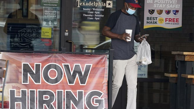 A customer wears a mask and looks at their cell phone as they carry their order past a now hiring sign at an eatery in Richardson, Texas, Wednesday, Sept. 2, 2020. The U.S. unemployment rate fell sharply in August to 8.4%  from 10.2% even as hiring slowed in August as employers added the fewest jobs since the pandemic began.