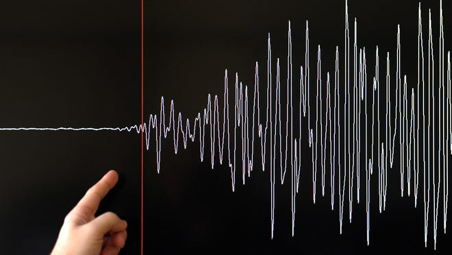 A technician of the French National Seism Survey Institute (RENASS) presents a graph on March 11, 2011 in Strasbourg, Eastern France, registered today during a major earthquake in Japan.