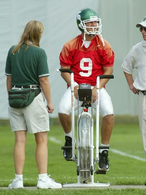 Flanked by then associate athletic trainer Sally Nogle, left, and head athletic trainer Jeff Monroe, right, MSU quarterback Jeff Smoker rides an exercise bike during practice Tuesday, Sept. 16, 2003, in East Lansing, Mich.