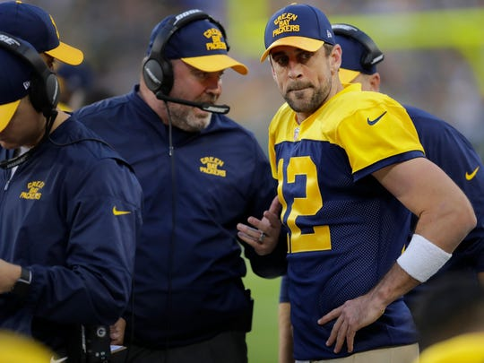 Green Bay Packers head coach Mike McCarthy talks to Aaron Rodgers on the sideline.