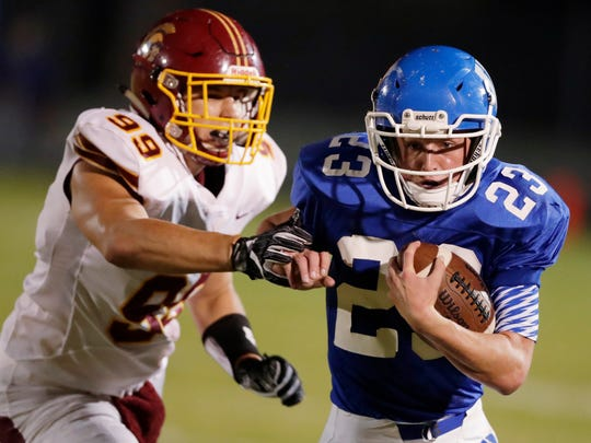 Wrightstown's Jacob Klister (23) runs from Luxemburg-Casco's Nathan Coisman (99) in a high school football game at Wrightstown High School on Friday, October 6, 2017 in Wrightstown, Wis.