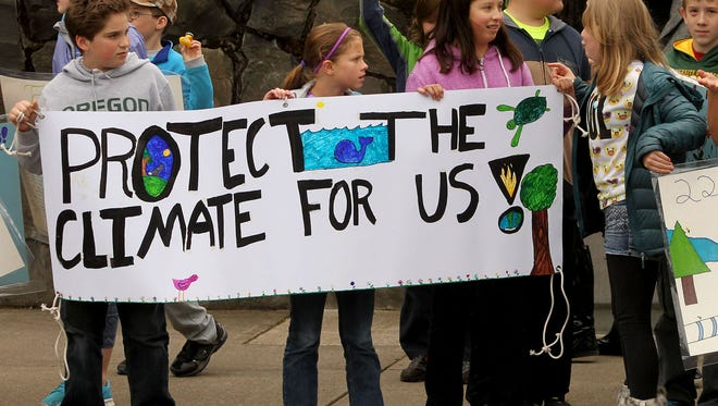 Fifth grade students from Edison Elementary School hold signs in front of the Lane County Courthouse in Eugene, Ore., Tuesday, April 7, 2015. The students were rallying in support of two local youth, Kelsey and Olivia Chernaik who's climate change case was being heard before Judge Karsten Rasmussen Tuesday. (AP Photo/The Register-Guard, Chris Pietsch)