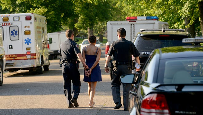 A woman is escored by officers from Lansing Township and East Lansing to an East Lansing police squad car Wednesday, June 10, 2015, after she was taken from the scene where more than 75 cats were discovered in a house in the 1700 block of the Groesbeck neighborhood.