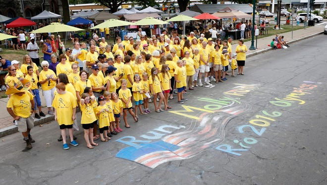 "A group of approximately 80 people dressed in yellow ""Run, Molly, Run"" shirts gather for a photo Thursday at Wisner Market. The day celebrated Elmira native and Olympian Molly Huddle."