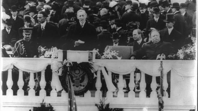 Woodrow Wilson speaking at his first inauguration on the east portico of the U.S. Capitol, March 4, 1913, with the Great Seal of the United States hanging below him