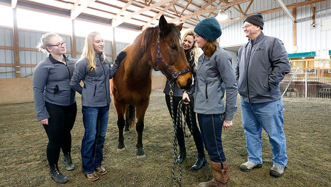 Members of Free SPIRIT Riders of Fond du Lac interact with one of the 17 horses they have at the facility Wednesday, Jan. 24, 2018. From left to right are Bridget Grzywacz, riding instructor, Monica Schaefer, head riding instructor, Alicia Hans, program coordinator, Elizabeth Karrmann, equine manager and Executive Director Paul Osterholm Sr.