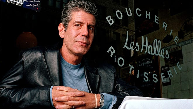 Anthony Bourdain,the owner and chef of Les Halles restaurant, sits at one of its tables in New York, Dec. 19, 2001.