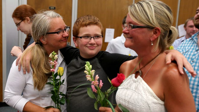 Aiden Murphy, 11, smiles as his mothers Kimberly Trojan (left) and Jackie Cornell wait  for their marriage license June 25, 2014, at the City-County Building.