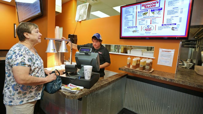 "Sandy Compton (left) places her order Sept. 2, 2014, with Chance Honeycutt at the Roscoe's Tacos franchise location at 6845 S. Bluff Road, Indianapolis. ""I'm so happy to see this one open,"" she said. The original location in Greenwood is where she came to love the food."