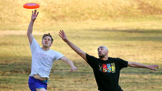 Stuart Sayger (left) of Indianapolis plays Frisbee with Justin Ware of Indianapolis at the American Legion Mall on March 18, 2014.