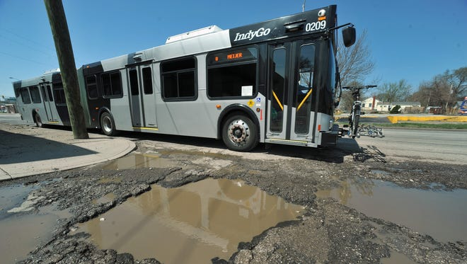 An IndyGo bus is reflected in the standing water in potholes at the intersection of Washington Street and Forest Avenue on  April 16, 2014.