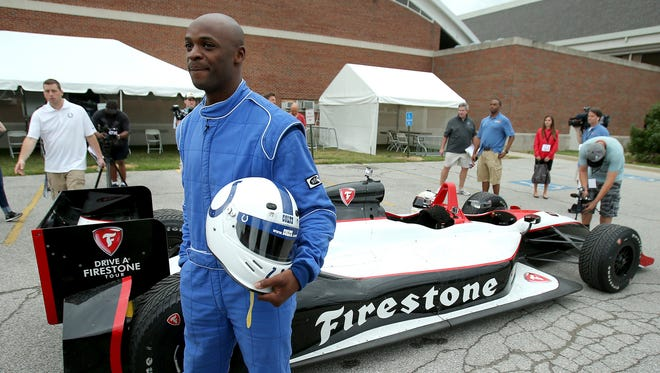 Indianapolis Colts wide receiver Reggie Wayne arrives in a two-seater IndyCar on the first day of training camp, on Wednesday, July 23, 2014, at Anderson University.