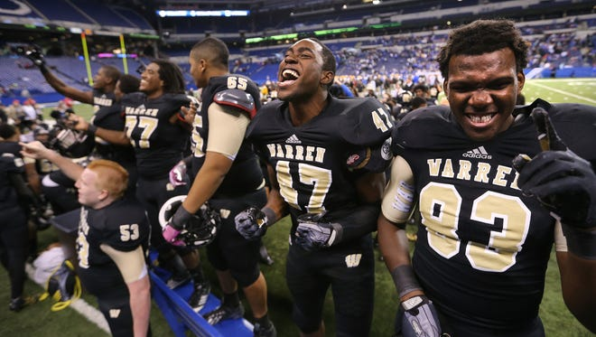 The Warren Central team scream in celebration after beating Carmel in the IHSAA Class 6A State Football Finals held at Lucas Oil Stadium on Sat., Nov. 30, 2013.
