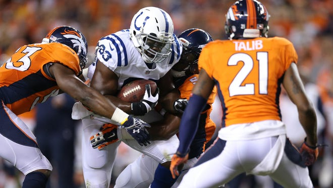 Indianapolis Colts Dwayne Allen gets swarmed by the Denver Broncos defense in the second half. The Indianapolis Colts play the Denver Broncos Sunday, September 7, 2014, evening at Sports Authority Field at Mile High in Denver CO.
