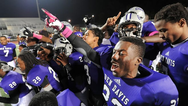 Ben Davis player Lesley Leon and his teammates celebrate their 28-24 win over Carmel after their game held at Ben Davis High School on Friday, October 18, 2013. Matt Detrich / The Star