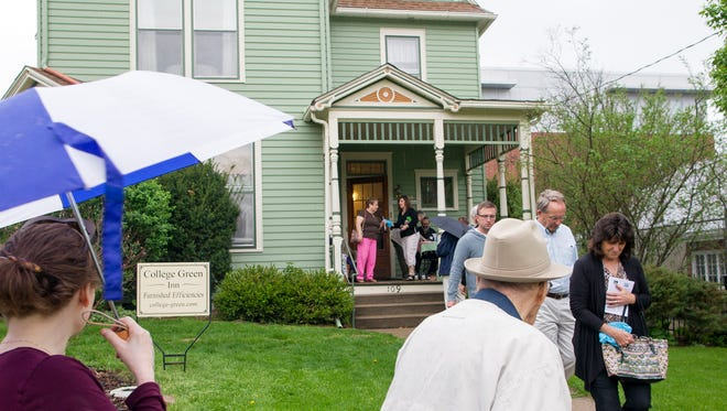 Rain falls as guests make their way to College Green Inn on Sunday on Johnson Street in Iowa City.