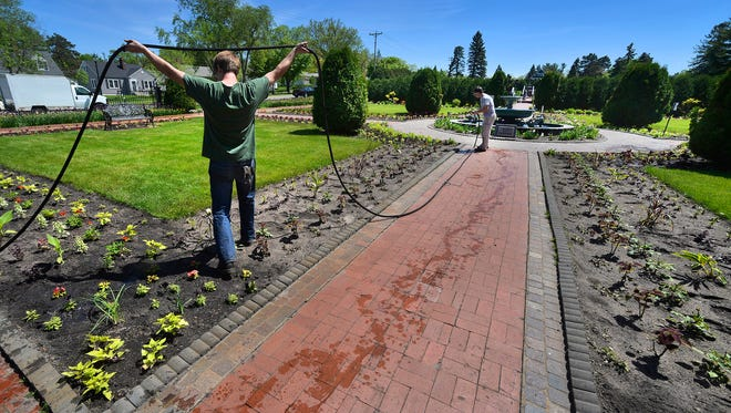 Munsinger-Clemens Gardens Horticulturists Jim Scully (left) and Chris Rouw take on the task of watering the new plantings in the gardens Thursday in St. Cloud. Some home gardeners saw weather-related delays in planting.