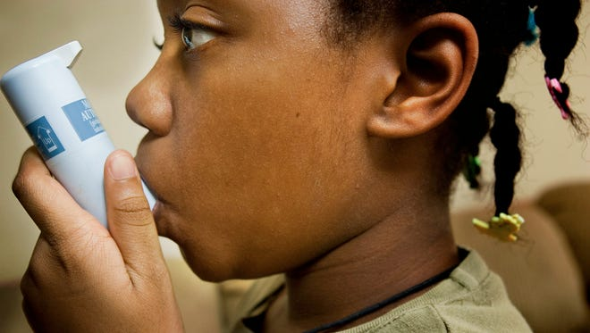 Mamako Johnson, 9, uses her inhaler for her asthma.  Her mother, Andrea, says the cost of insurance and co-pays is forcing them to postpone doctor visits and juggle expenses.