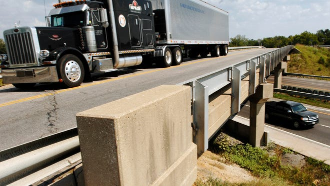 A truck drives on the Highway 40 bridge over I-70 near Midway, Mo.