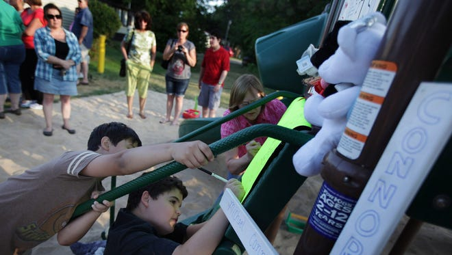 During a vigil Jaden Millet, 8 center and his friend Demetrius Snell, 9 write a message in remembrance of Michael Conner Verkerke, 9 who was fatally stabbed on Monday evening on this playground at the Pinebrook Village mobile home park in Kentwood, Mich., on Wednesday.