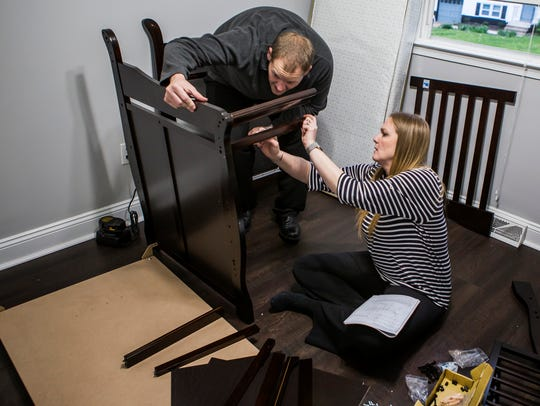 Janeen and Sean Feck assemble a crib for their soon-to-be