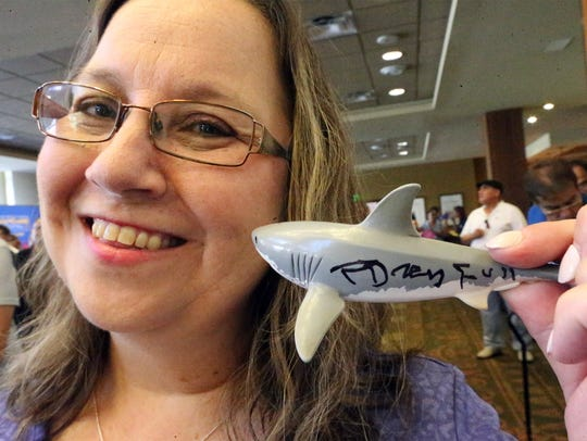 Zita Meyer of El Paso shows a small plastic shark she