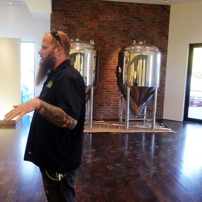 Chad Petit, co-founder of Hydra Beer Co., shows what