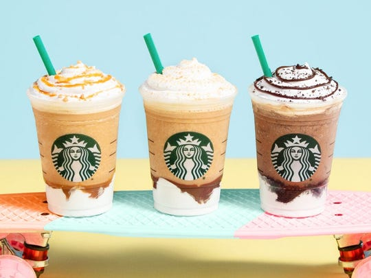 Three Starbucks Frappuccinos sitting on a skateboard