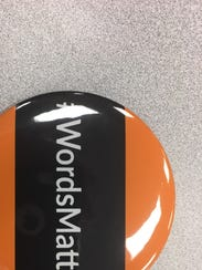 """Those who want Anderson to change its name wear orange and black """"Words Matter"""" buttons."""