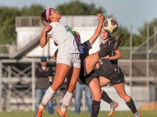 Colts Neck's Lauren Feaster and Middletown North's Kristen Gambardella battle for ball near midfield.