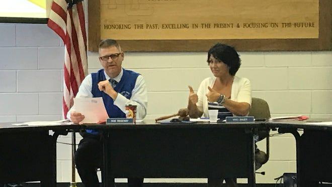 Harper Creek Community Schools board President Vikki Bauer gestures as Superintendent Rob Ridgeway addresses the audience Thursday.