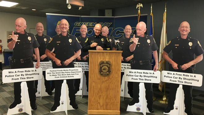 Green Bay Police chief Andrew Smith stands among nine life-size cutouts of himself, during a Monday press conference at the department's training center. The cutouts are part of a new anti-theft initiative.